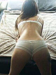 Стройная девушка раздевается на кровати и хочет секса