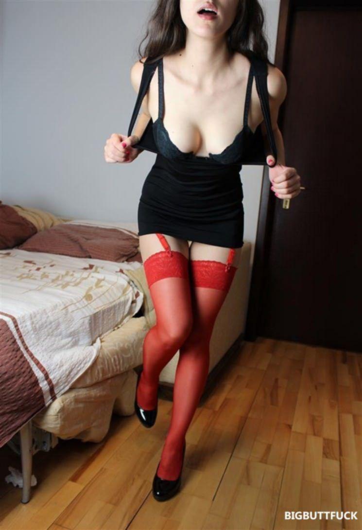 Худенькая брюнетка в красных чулках показывает свои прелести на фото